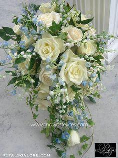 Rosas blancas en cascada, lirios del valle y delphinium en color azul cielo