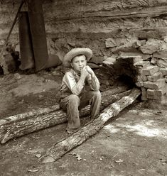 """July 1939. """"Ten-year-old son of tobacco sharecropper can do a 'hand's work' at harvest time."""" Seen here feeding logs into the fire next to flue of the curing barn. Granville County, North Carolina. Medium-format nitrate negative by Dorothea Lange for the Farm Security Administration."""