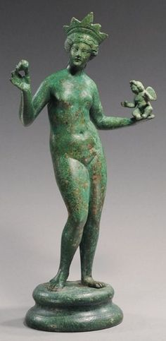 A Roman bronze statue of Venus holding Eros and a pomegranate.