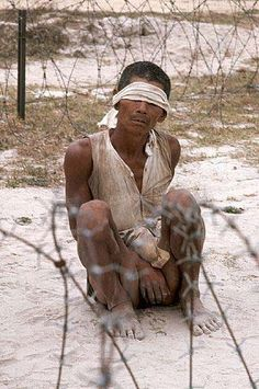 A suspected Vietcong captured by the US. He squats blindfolded behind a barbed wire enclosure, 1969 (8)