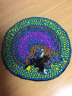 Seed bead coaster . Look closely and you will see a bird .