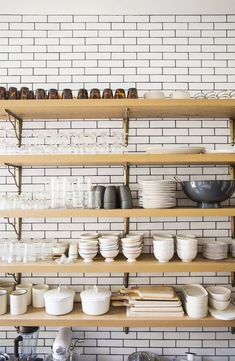 White Subway tiles, black grout, wood open shelving and brass/gold hardware