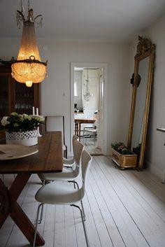 grand lustre, table en bois et sol en lattes blanches