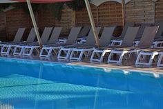 Transats de la piscine de la résidence de vacances Paese di Lava en Corse du Sud. La piscine est chauffée toute l'année. Les transats sont complétés de table basses qui permettent de savourer des cocktails et boissons rafraîchissantes disponibles au Bar Piscine