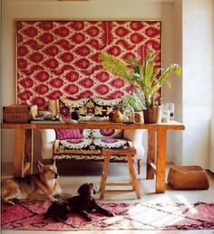 suzani drapead over settee, with framed vintage ikat behind. from elle decor.
