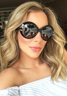 Helena Lunardelli usando um óculos da Omega, que acabou de lançar uma coleção de óculos de sol que remetem a elementos e traços dos modelos icônicos de peças da marca.