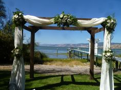 All white arbor flowers for wedding ceremony.  white gerbera daisies.  At the lake.  Muslin draping.