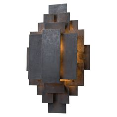 Inspired by the 1950s brutalist movement, this one-light, iron sconce is crafted out of hand cut geometric shapes, welded together into a tribal-like pattern. The wax finish helps keep the sconce natu