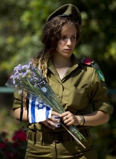 black female idf soldiers | An Israeli soldiers prepares to place an Israeli flag with a black ...