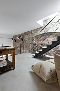 Exposed brick accent wall with finished white ceilings and some black metal accents combine to create clean loft aesthetic