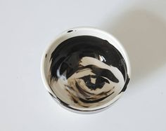 An Abstract Eye Bowl that is artfuland fun in Black and White, An Eye Bowl Collection of Porcelains Bowls . Porcelain at is most modern, that is upgraded to fine art, One of Kind, Hand Painted Bowl. This would be a beautifu gift for that friend and loved one that loves art in the most modern ad unusual way. A great gift for the home for people that love simple modern elegant things.  The bowl is 2.25 inches high and 4 inches across. Made on the potters wheel, then fired, painted and fired…