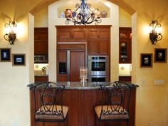 This small bar serves as a transition between the kitchen and dining room. Wrought iron bar stools match the large wrought iron chandelier hanging in the kitchen.