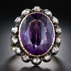 Large Antique Amethyst and Diamond Ring A dynamic, dramatic and quite sizable early-Victorian - verging on Georgian - bauble featuring a glorious deep purple faceted oval amethyst with a buff-top table. The gemstone glows from within a yellow gold bezel and is framed all around with glistening rose-cut diamonds set in well-oxidized silver bezels. The marvelously sculpted ring shank is comprised of three distinct leaf motifs which merge under the finger. Regal splendor!     Price: USD…