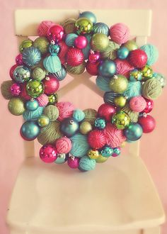 the balls of yarn are such a nice touch to the traditional ornaments that make up this wreath! happy colors.