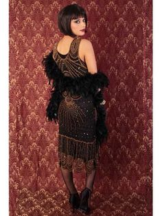 "<p>The stunning 1920s style vintage reproduction ""Sheba"" flapper dress is made exclusively for Blue Velvet Vintage. You won't find this anywhere but here! An authentic roaring 20s look for art deco themed dances, Great Gatsby weddings and formal events.</p> <p>•Meticulously hand beaded in a deco design of bronze gold sequins and bronze gold and purple/blue irridescent beading on heavyweight sheer black mesh, just like the originals.<br &#x..."