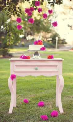 If you planning an outdoor party for your kids and have the cake table outside, bring the table under a branch and dangle the pom poms