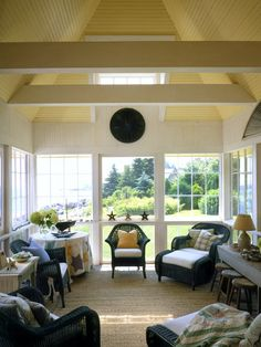 The yellow ceiling is a surprising touch in this cozy porch. I like the use of the old quilt as a table cover. Coastal Living