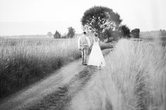 Bride and Groom walking hand in hand down a two track dirt road with grass along the sides with the dog.  Black and white shot.