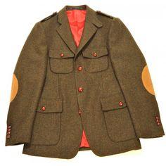 Veste saharienne en Tweed verte avec coudières en alcantara. Dessous de col en feutre rouge et boutons de cuir marrons. Poches plaquées à rabat, trois boutons et doublure rouge vif avec mignaunette aux manches. Epaulettes, patte de col et double fente au dos.