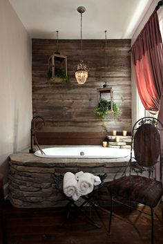 aged wood wall, stone inset tub, farmhouse faucet, great touches of greenery in rustic lanterns