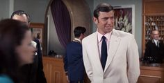 George Lazenby's first suit as Bond is none of the above. It's a cream linen suit, appropriate for a warm resort in Portugal. Lazenby's Bond is introduced with a more fashionable and rakish suit, with a more suppressed waist, a shorter jacket length, a more rounded front skirt opening, slanted pockets, deeper double vents and flat-front trousers.