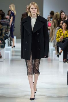 A navy peacoat and fishermans knit tempers the sex-appeal of a sheer lace pencil skirt. A stellar start at Nina Ricci from Guillaume Henry.