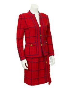1970's classic red Adolfo knit suit with navy window pane pattern and adorable fringed edges. Over sized gold plated buttons trim the cuffs of the jacket and decorate the front of the skirt. Lots of g