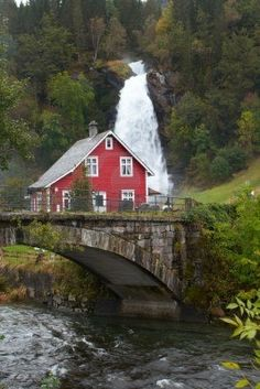 traditional Norwegian wooden house and old arch bridge with waterfall in the distance Stock Photo - 5738154