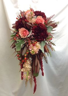 Sangria and blush bridal bouquet with safari sunset, stock, roses, hypericum berries, astilbe, amaranthus, carnations with dusty miller accents by Nancy at Belton Hyvee.