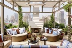 Siegel created the trellis and fireplace for the rooftop terrace, above the master bedroom. The slate paving is from Stone Source, the daybeds and glass-top tables are by Dedon, and the pillows are made of Sunbrella by Les Toiles du Soleil and Janus et Cie fabrics. The plantings are by Miguel Pons Landscaping and Matthias Kirwald Landscaping.