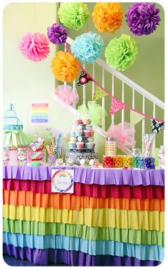 Rainbow birthday party theme candy table, tissue poms, handmade crepe paper rainbow table skirt, and more.