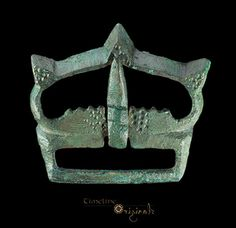 Large Medieval 'Crown-Shaped' Buckle. 13th-14th century AD. Cast bronze, 56 grams, 62.23 mm. A rectangular open plate with serrated forward edge and recess for the tongue; the loop D-shaped with three cast triangular projections to the forward edge; the tongue D-section with square block to the upper face; to the rear edge a rectangular-section bar for attachment to the belt; to the upper faces of the plate and loop, punched-point detailing.