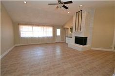 Spacious family room featuring tile floors, raised ceilings, recessed lighting, ceiling fan with light fixture, wood burning fireplace, doo...