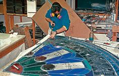 Man in a protective face mask using tools to work on a stained glass window on a table.