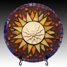 "Sun Circle by Carol Boruta  - This piece is made with #Purple, #Orange and #Yellow stained glass and orange smalti. It is grouted in a sable #Brown. Beautiful with the sun shining on it in your favorite room.  The #mosaic is 15"" diameter and comes with a Black plate stand. $225.00 On Artful Vision, a portion of your purchase is donated to a participating non-profit of your choice. #home #decor"