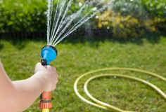 Woman holding garden hose watering the lawn
