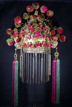 Chinese wedding tiara adorned with a multitude of happiness and longevity signs mounted on tremblant. The lower element is of silver, and features two embossed dragons; from the upper part emerge the eight immortals and three phoenixes. A curtain of bead fringe hides the bride face. Long silk tassels on each side.        Early 20th c