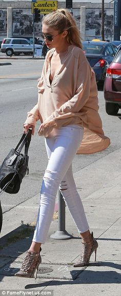 Simply stylish:Gigi rocked the quintessential off-duty model look, wearing a pair of white distressed jeans with a loose fit apricot top that hid her slender frame