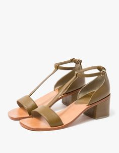 From Rachel Comey, a modern T-strap leather sandal in Olive. Featuring a pebbled olive upper, an open toe t-strap upper with adjustable ankle strap, small brass buckle, suede lined heel box and leather heel pad, leather sole, and coordinating leather stac