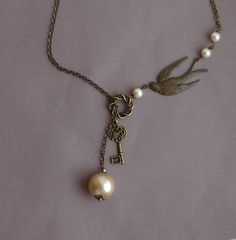 Vintage Style Swallow Key and Ivory Pearl Lariat -- Antiqued Brass Necklace. $26.00, via Etsy.