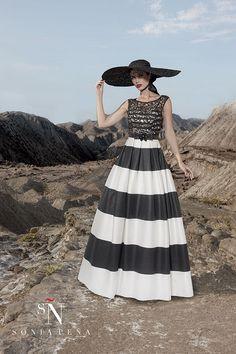 Vestido de fiesta largo con falda evasé de rayas en blanco y negro. Cuerpo de red sobre palabra de honor....