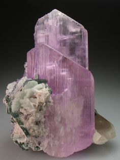Spodumene var. Kunzite with Elbaite and Apatite | ©Crystal Classics Mawi Pegmatite, Afghanistan. The unusually rich lilac-pink color in this specimen indicates the crystal are high in Lithium.