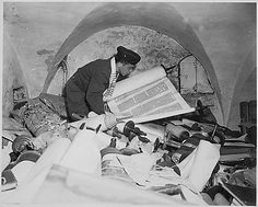 """In the cellar of the Race Institute in Frankfurt, Germany, Chaplain Samuel Blinder examines one of hundreds of """"Saphor Torahs"""" (Sacred Scrolls), among the books stolen from every occupied country in Europe., 07/06/1945"""