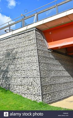 Recycled concrete crushed to form Gabion caged basket in bridge abutment and retaining wall behind a galvanised steel mesh Stock Photo