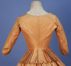 STRIPED SATIN GOWN, 1770's. 2-piece ivory taffeta with peach pinstripe, front lacing bodice with narrow over elbow length sleeve, back having stitched down pleats opening to form peplum with furbelows, linen lining with waist tie, skirt open at sides with linen ties, narrow pleats to either side of center front, skirt lined in cotton muslin
