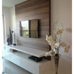 Painel de sala de estar em madeira com prateleiras e gaveteiro branco, com adornos flores decorando.