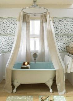 A Kohler cast iron clawfoot tub with Vapour Blue glazing just on the interior beckons in this KBIS & Country Home Magazine 2007 kitchen designed by Erica M Smith CKD CBD
