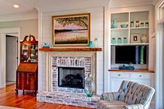 The fireplace brick and surround and the mantel are all antique; they came out of a historic building in downtown Charleston. V-groove tongue and groove ceilings and heart pine flooring also add vintage cottage style, while lovely glass drawer pulls play off the owners' collections. Built-in shelves and cabinets provide more display space as well as places in which to tuck away electronic components.