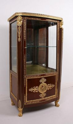A fine Russian mahogany and ormolu mounted vitrine, late 19th centruy, fitted with a single glazed door flanked by ormolu Egyptian mask caryatid pilasters, enclosing a single glass shelf and above a cupboard door, formal motifs throughout, the interior cupboard shelf bearing an inscription in cyrillic and dated '18', 132cm high, 72cm wide, 42cm deep. <br> In good condition. <br>
