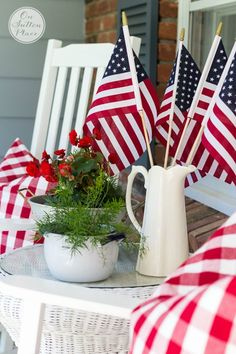 Easy patriotic outdoor decor | Just put a few craft store flags in a pitcher and add some plants with red blossoms.